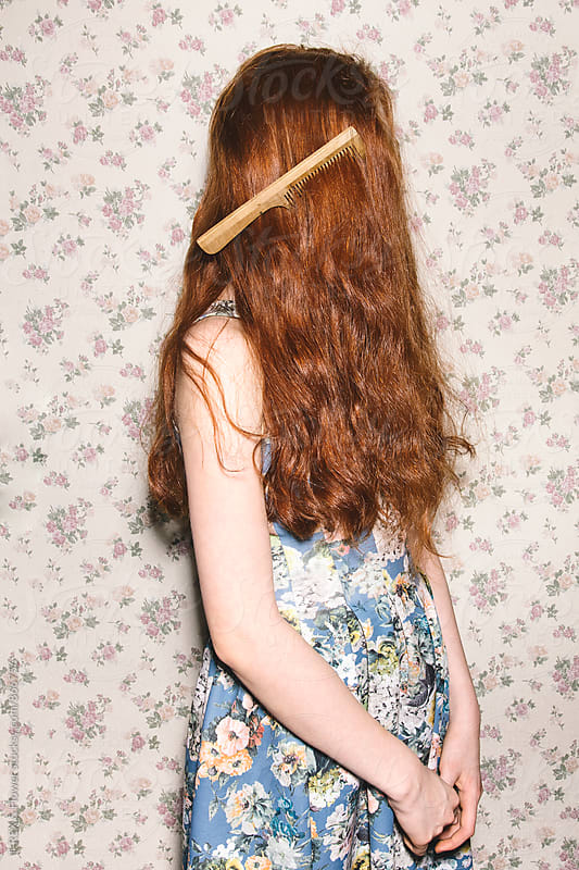 Side view of red-headed woman with comb in hair by T-REX & Flower for Stocksy United
