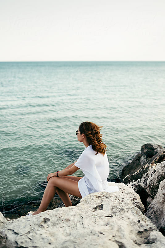 Young woman sitting on rocky beach by Pixel Stories for Stocksy United