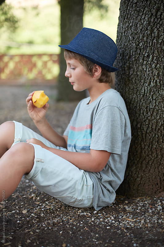 Young boy sitting in the yard and eating fruit by Miquel Llonch for Stocksy United
