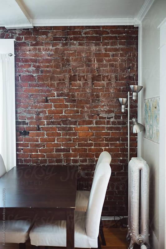 Kitchen table in a small dining room with a brick wall by Kristine Weilert for Stocksy United