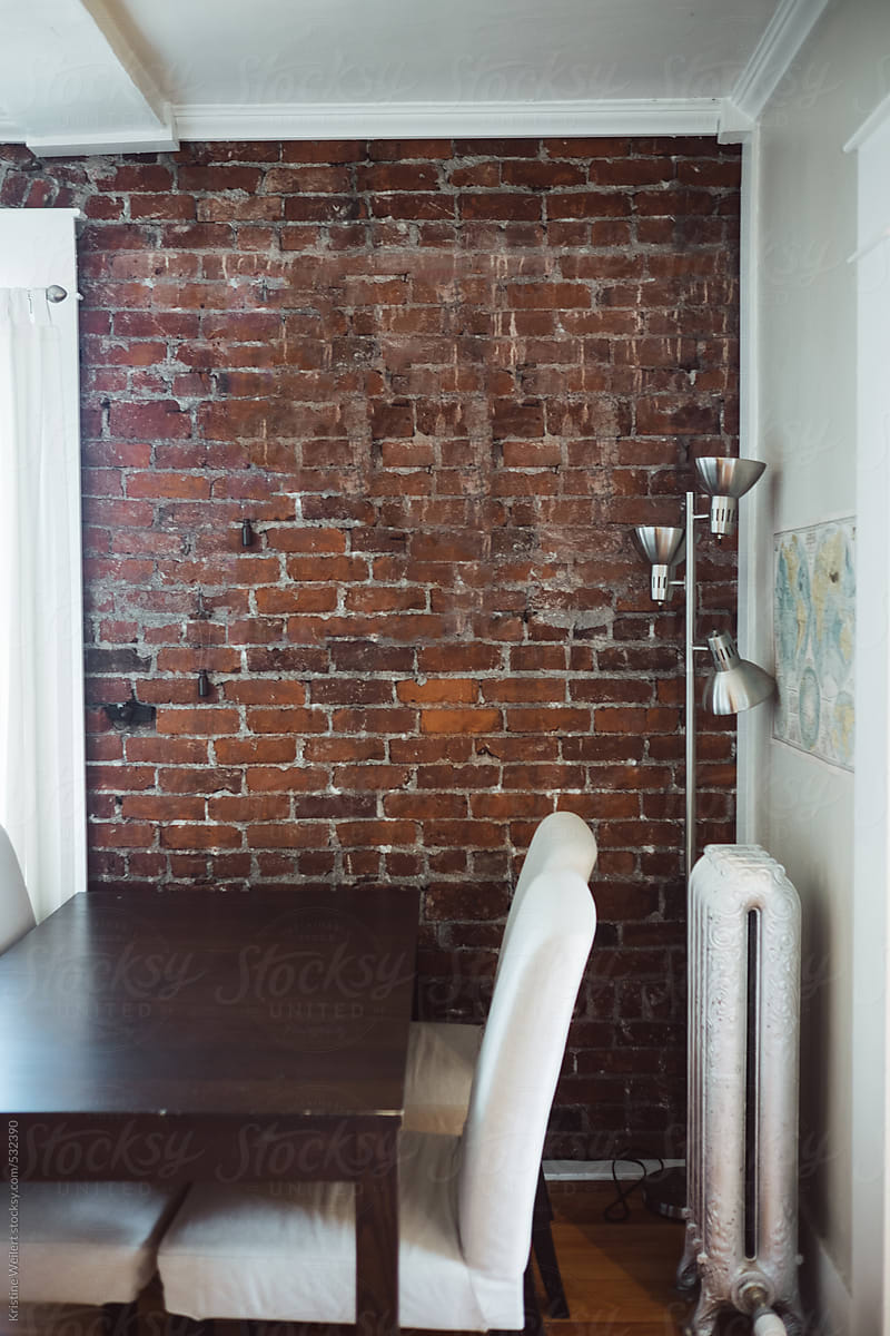 Kitchen Table In A Small Dining Room With A Brick Wall By Kristine Weilert Stocksy United