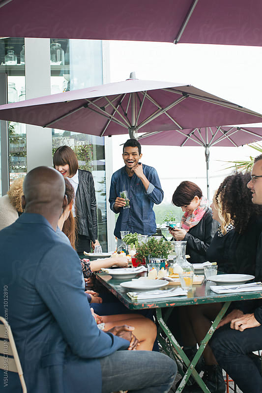 Group of Friends Sitting on Restaurant Rooftop Terrace and Having a Laugh by Julien L. Balmer for Stocksy United