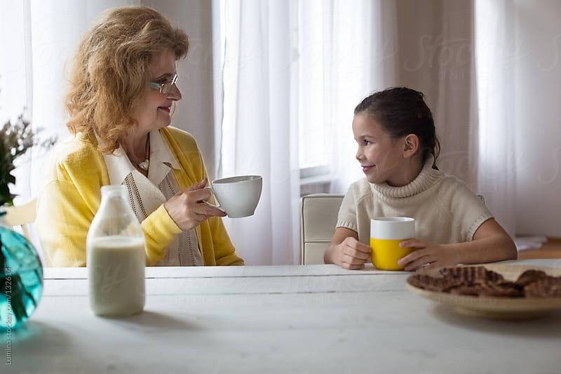 Grandma and Granddaughter Having Breakfast by Lumina for Stocksy United