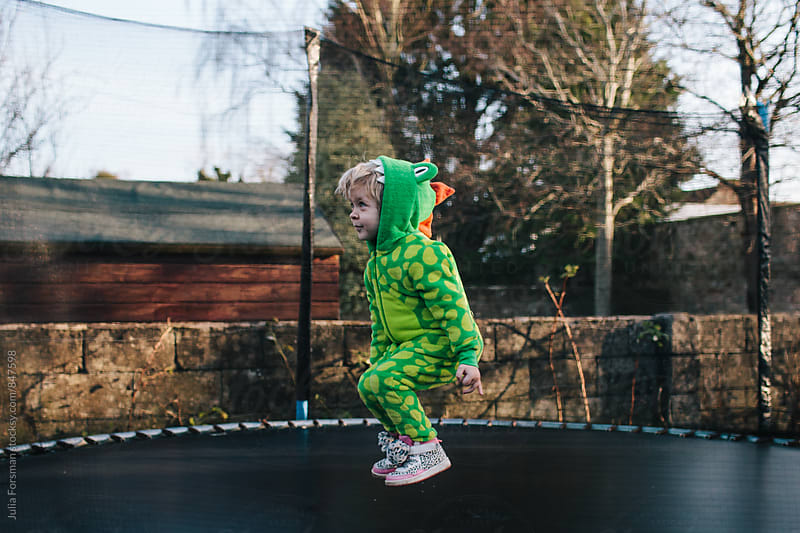 A child in a dragon suit bounces on a trampoline. by Julia Forsman for Stocksy United