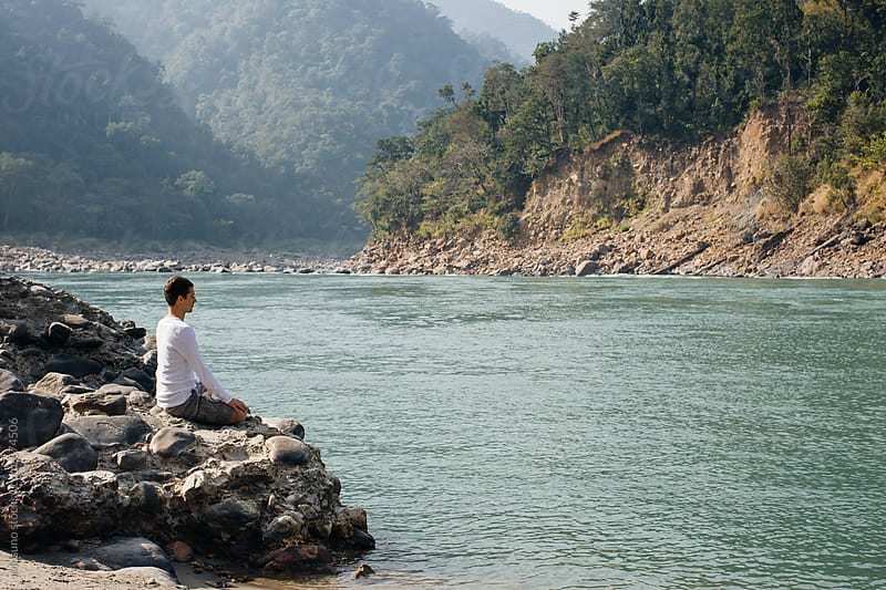 Man Meditating by the Holy Ganges River by Mosuno for Stocksy United