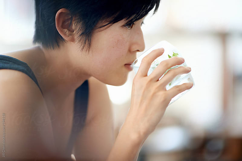 Asian woman drinking a cocktail  by Jill Chen for Stocksy United