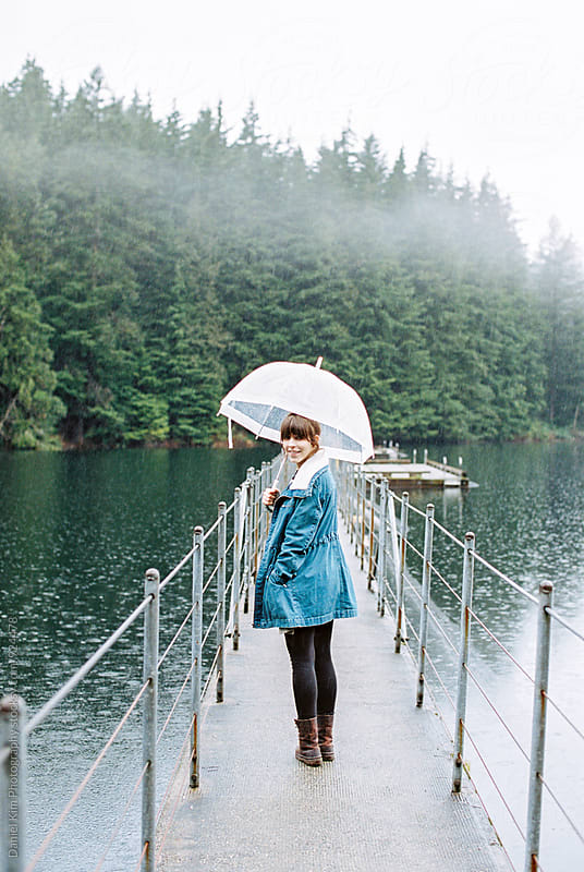 Woman holding umbrella on lake by Daniel Kim Photography for Stocksy United