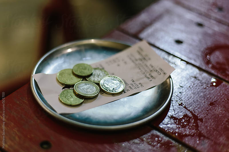 Euro money change and receipt on plate at restaurant bar table by Matthew Spaulding for Stocksy United