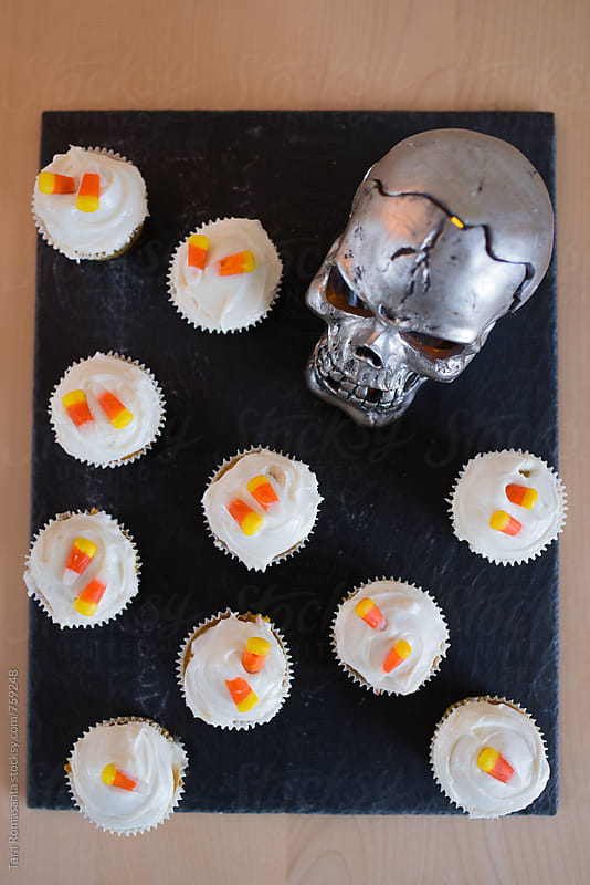 Pumpkin cupcakes with candy corn and cream cheese icing for Halloween by Tara Romasanta for Stocksy United