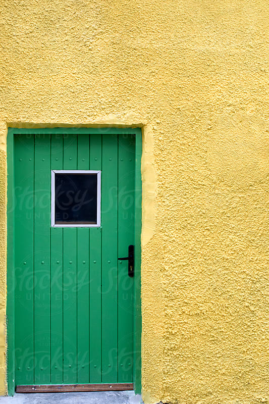 Green door and yellow wall by Pixel Stories for Stocksy United