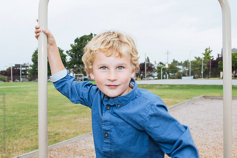 A blonde boy looking at camera at a school playground by Ania Boniecka for Stocksy United