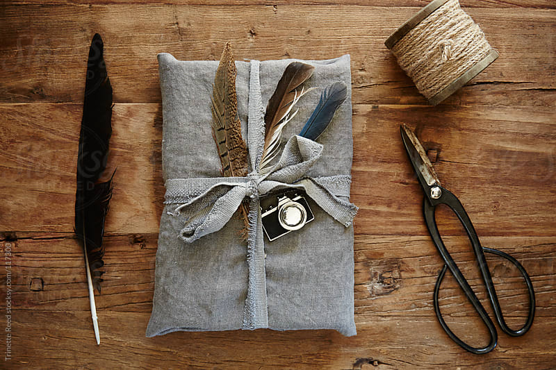 Still life of hipster linen wrapped gift with feathers by Trinette Reed for Stocksy United