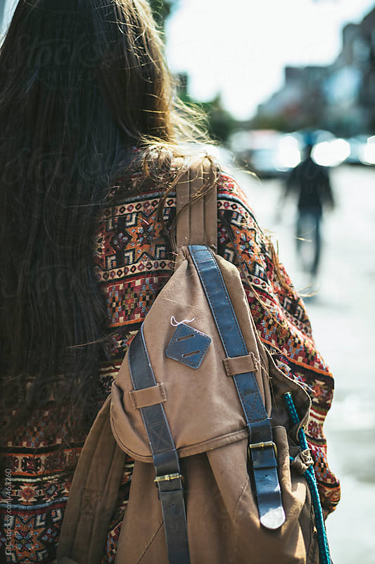 Woman walking in the street with a backpack by GIC for Stocksy United