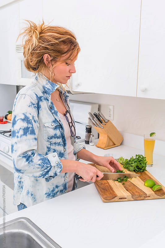 Woman Chops Fresh Herbs and Onions in the Kitchen by suzanne clements for Stocksy United