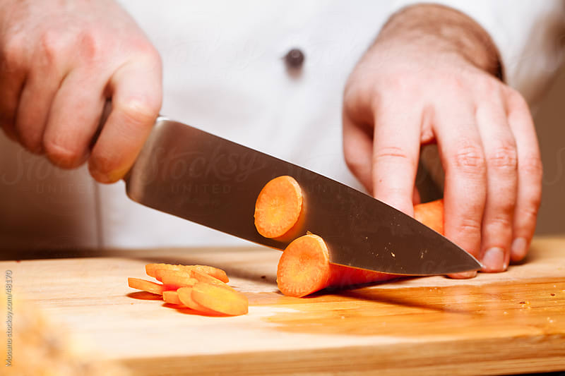 Man Cutting Carrots by Mosuno for Stocksy United
