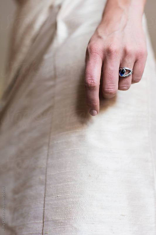 A woman's hand wearing an beautiful rin against gold, silk fabric. by Holly Clark for Stocksy United