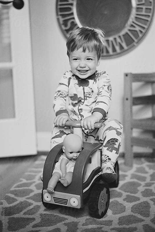 Smiling young boy sitting on a toy car by Jakob for Stocksy United