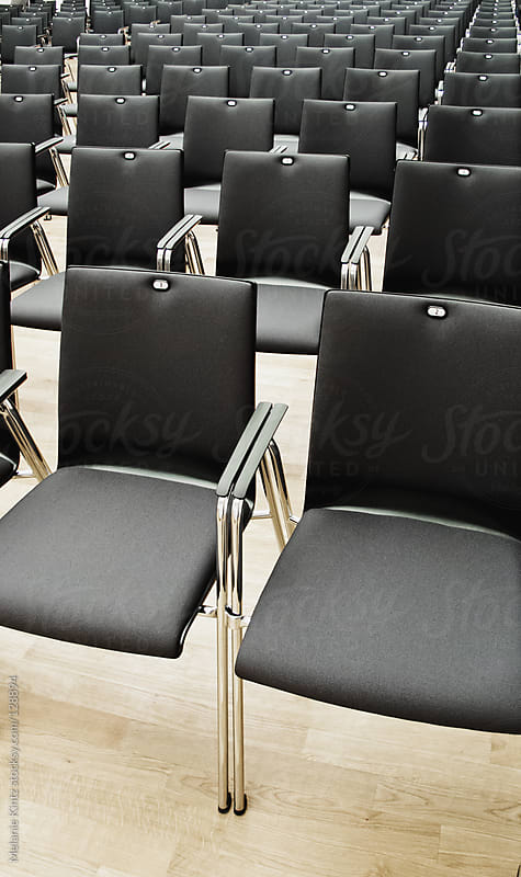 Rows of empty chairs in a meeting room by Melanie Kintz for Stocksy United