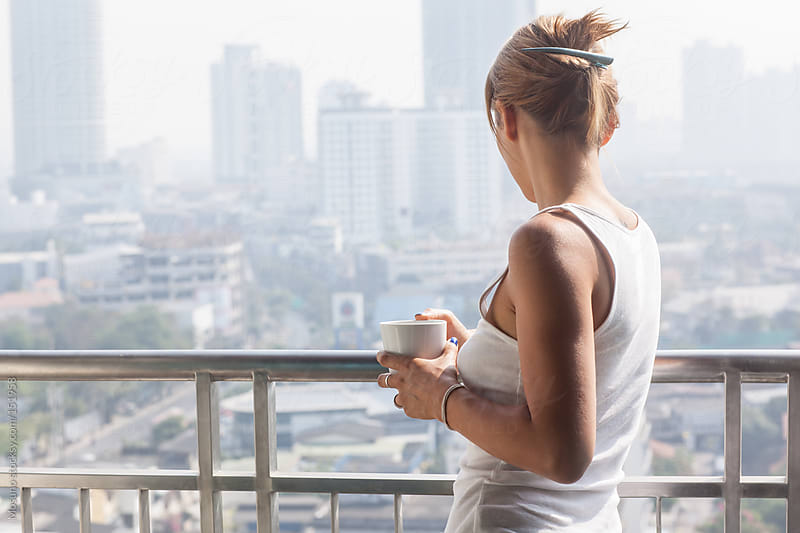 Woman Drinking Coffee and Enjoying Bangkok Skyline  by Mosuno for Stocksy United