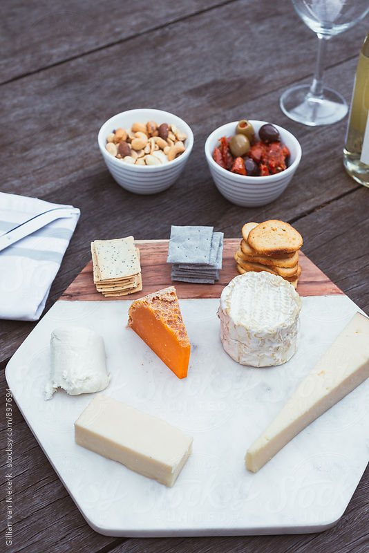 cheese platter with wine by Gillian Vann for Stocksy United