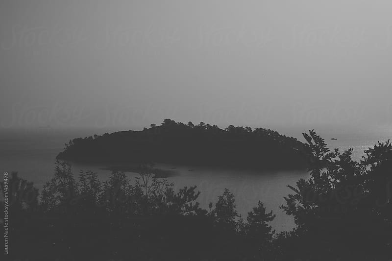 Island covered in fog and mist by Lauren Naefe for Stocksy United