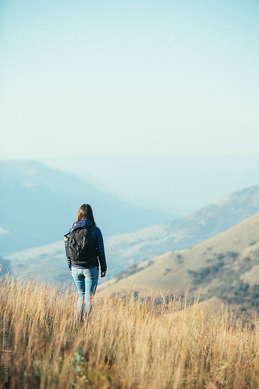 Hiker with backpack overlooking a scenic valley by Micky Wiswedel for Stocksy United