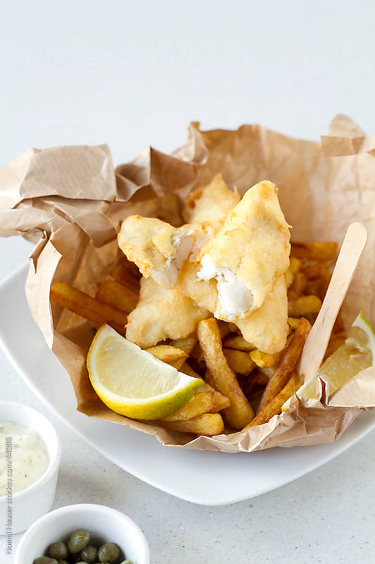 Fish and chips on brown paper with lemon wedge by Noemi Hauser for Stocksy United
