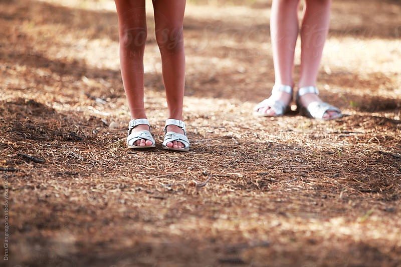 Two young girls lower legs standing side by side by Dina Giangregorio for Stocksy United