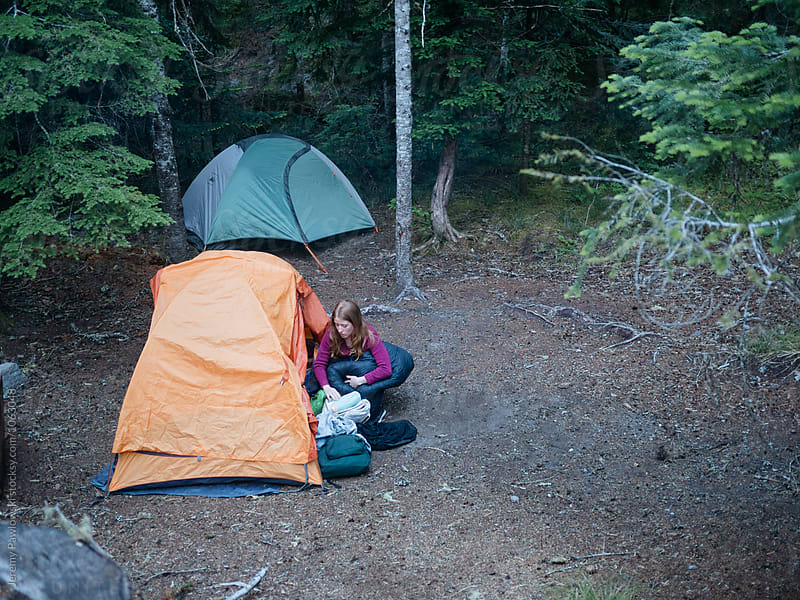 Young woman setting up tent and sleeping bag at campground in the woods. Washington, USA by Jeremy Pawlowski for Stocksy United