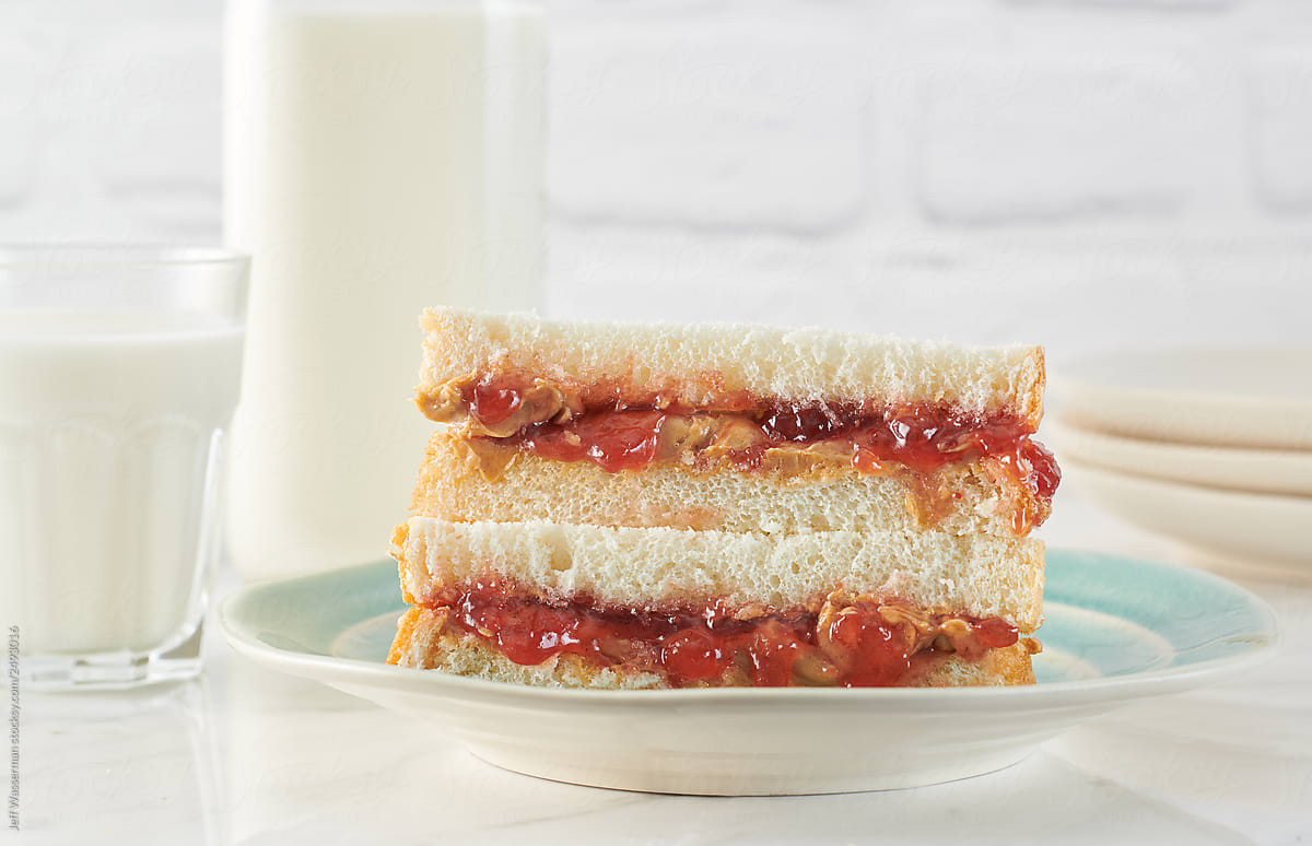Peanut butter and strawberry jam sandwiches on plate with milk