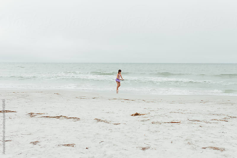 A girl in the distance running along the beach, wide angle by Amanda Worrall for Stocksy United