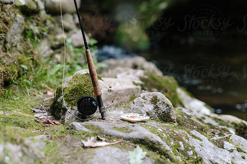 Fishing rod and reel with flies on side of river by Matthew Spaulding for Stocksy United