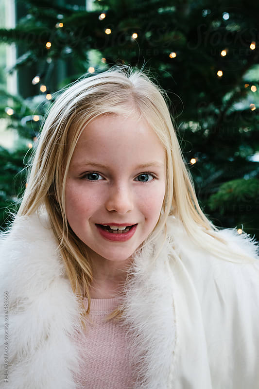A little girl in a fur wrap in front of a Christmas tree. by Helen Rushbrook for Stocksy United