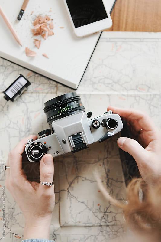 Girl changing film in a camera by Ellie Baygulov for Stocksy United