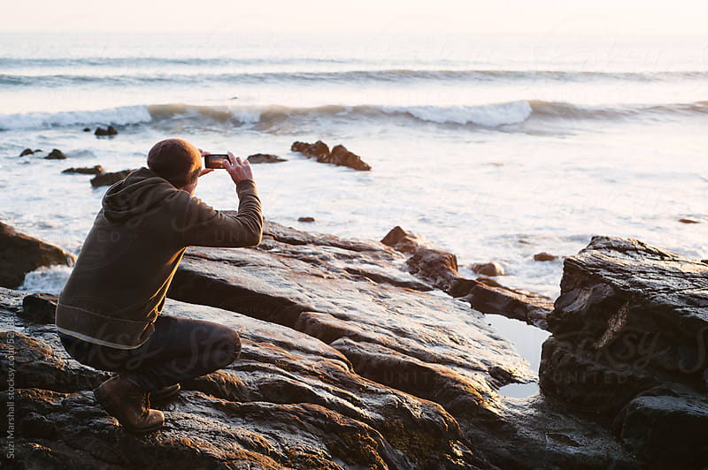 Man standing on rocks taking a photograph of the sea at sunset with his phone by Suzi Marshall for Stocksy United