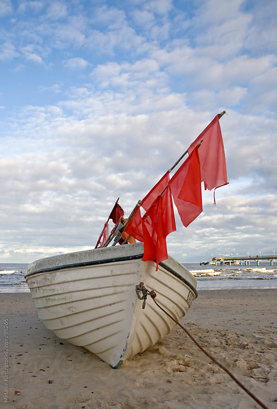 Fishing boat with red flags at the beach  by Melanie Kintz for Stocksy United