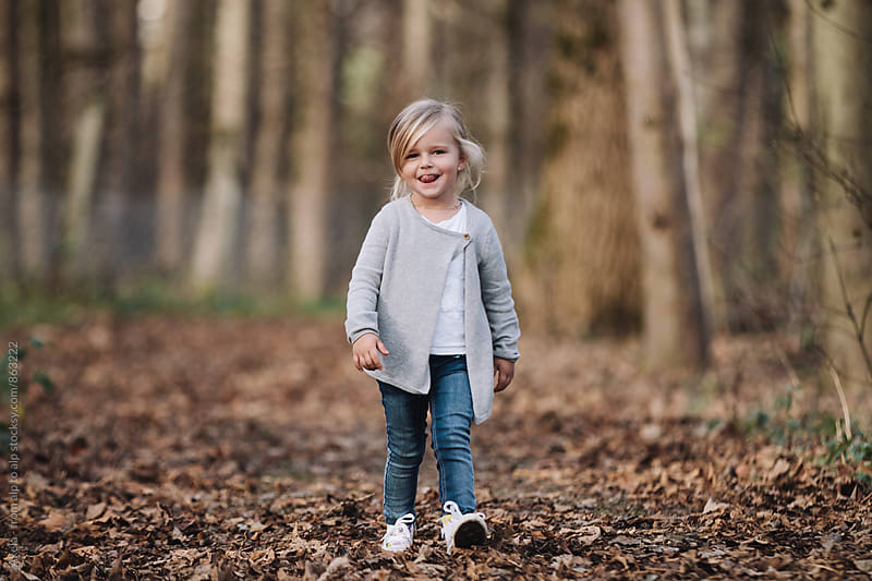 smiling trendy cute little girl walking in foliage covered forest by Leander Nardin for Stocksy United