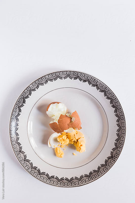 Broken boiled egg on a vintage plate by Vera Lair for Stocksy United