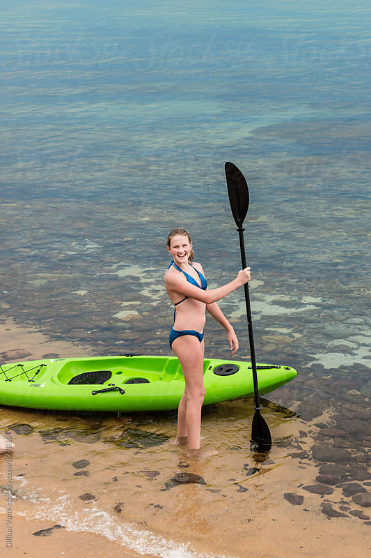 teen girl with kayak at the beach by Gillian Vann for Stocksy United