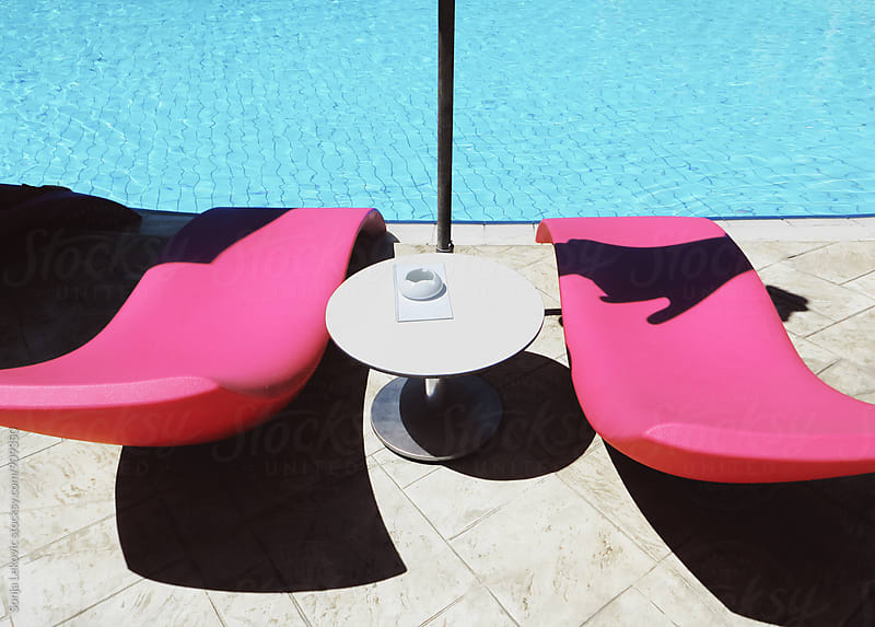 pink sun beds by the swimming pool by Sonja Lekovic for Stocksy United