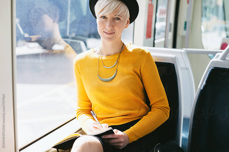 Portrait of a modern and chic woman sitting in the train of the city. by BONNINSTUDIO for Stocksy United