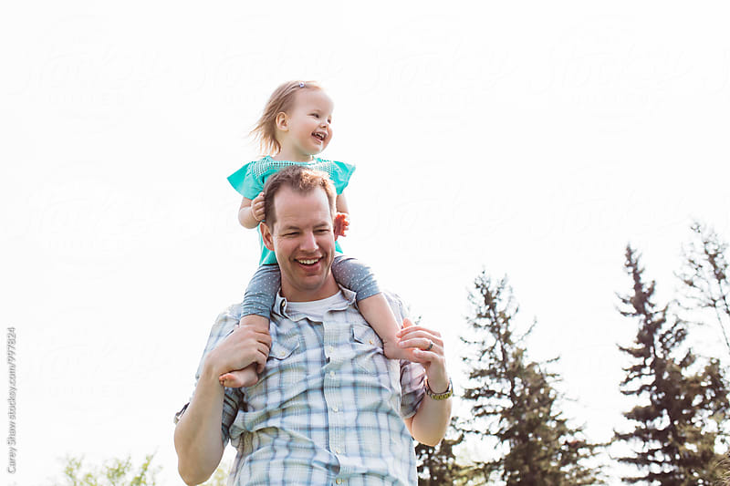 Happy young daughter sitting on fathers shoulders