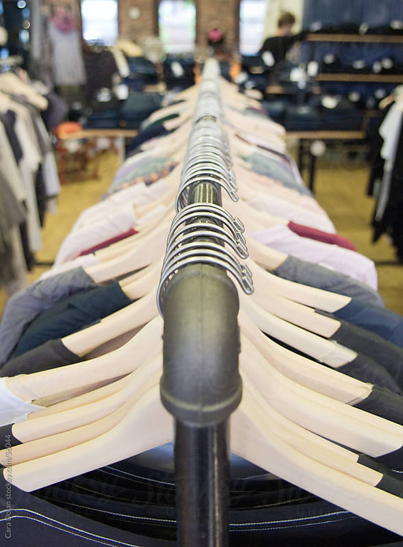 Rack of shirts on hangers inside a shop by Cara Slifka for Stocksy United