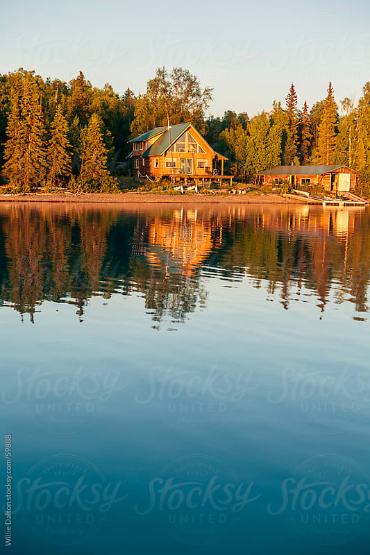Cabin and Boat House are Reflected by a Glassy Calm Lake by Willie Dalton for Stocksy United