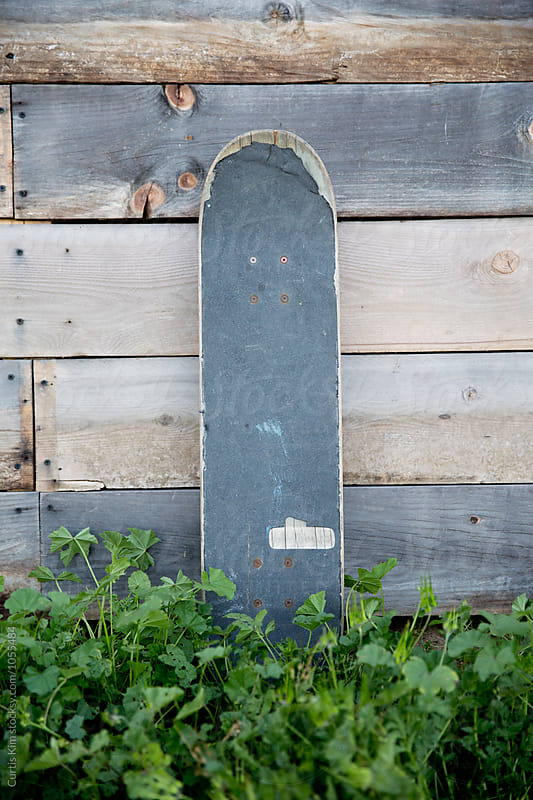 Skateboard leaning up against wooden fence by Curtis Kim for Stocksy United