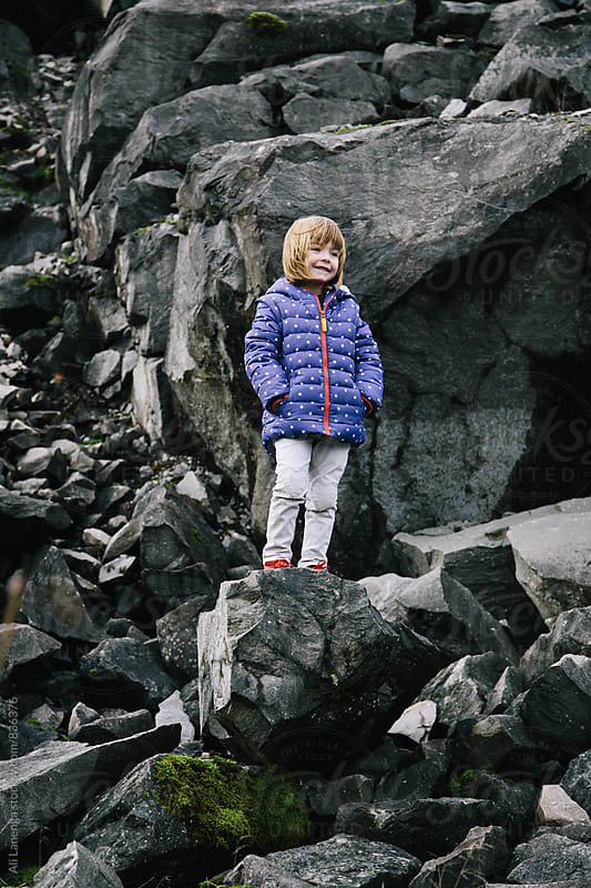 Child on rock by Ali Lanenga for Stocksy United