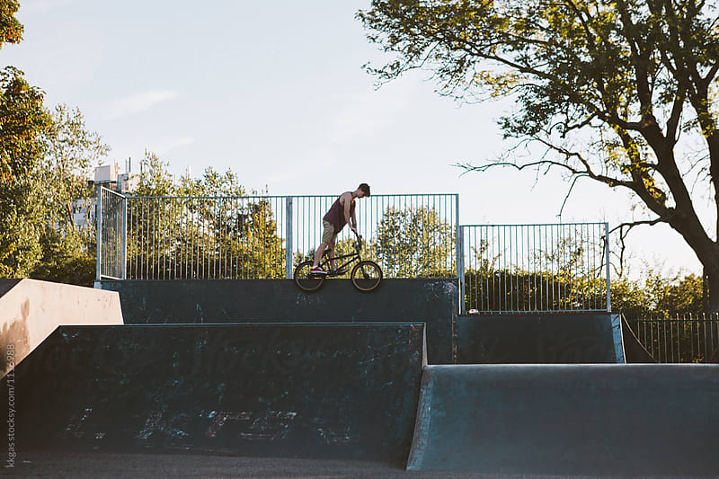BMX rider performing stunts and tricks on ramps in a skate park