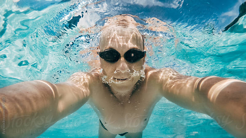 Man swimming in the pool looking at camera selfie by Ilya for Stocksy United