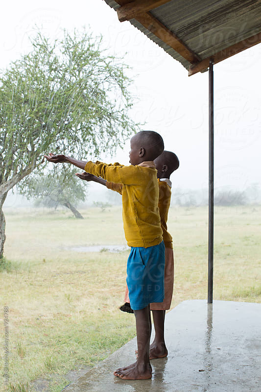 School children having fun in the rain. Kenya. by Hugh Sitton for Stocksy United