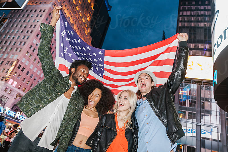 American Friends Having Fun with a USA Flag in Times Square, Manhattan, USA by VICTOR TORRES for Stocksy United